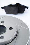 Car brake system components. Car ventilated brake disc in front and brake pads in back Stock Image