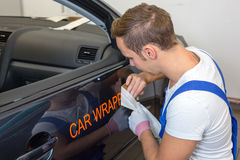 Car branding specialist puts logo with car wrapping film on automobile. Car branding specialist puts logo with car wrapping foil or film on vehicle door stock images