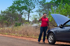 Car breakdown - African American woman call for help, road assistance. African American woman in car breakdown - call for help, road assistance in the tropics Royalty Free Stock Image