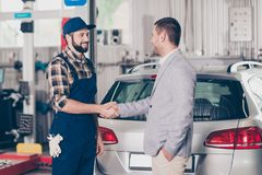Car breakdown, check condition, inspection, engineering, insuran. Ce, repair concept. e profile shot of satisfied businessman in classy suit shaking arm of Stock Image