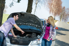 Car breakdown couple calling for road assistance. Men point engine Royalty Free Stock Image