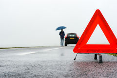 Car with a breakdown in the rain and fog. Man with an umbrella besides his broken car alongside a road in the middle of nowhere Stock Photos