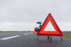Car with a breakdown in the rain and fog. Man with an umbrella besides his broken car alongside a road in the middle of nowhere Royalty Free Stock Photography