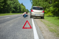 Car after breakdown on the roadside and red triangle warning sig Stock Image