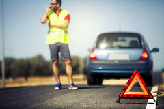 Car breakdown scene. Reflective triangle, with a man calling by phone, and a stopped car in the middle of the road Royalty Free Stock Images
