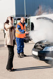 Car breakdown woman get help road-assistance man. Woman with technician help smoking engine car breakdown trouble accident Stock Images