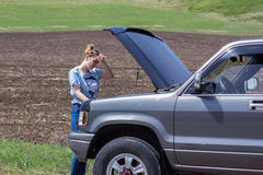 Car breaks on the road with the young woman. A beautiful young woman trying to repair the car Stock Photography