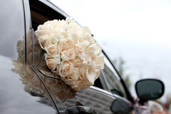Car and brides bouquet in a car window Stock Photo