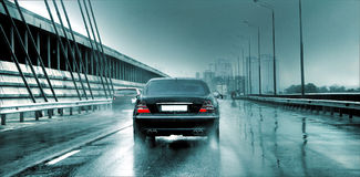 Car on the bridge. Black car goes on the bridge. There is a rain. Sparks of water fly from wheels. The car other car and a motorcycle overtake Stock Photography