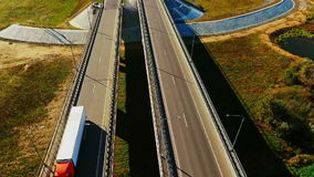 Car bridge over river. Drone view of highway bridge above river. Cars and truck driving along highway bridge. Highway road on river landscape. Cars moving on stock video footage