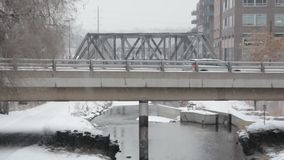Car on bridge on snowy day stock footage