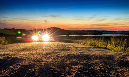 Car with bright light in beautiful mountain landscape sunset sun Royalty Free Stock Image