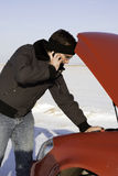 Car Broken Down. A young man is checking under the car hood while talking on a cell phone Royalty Free Stock Images