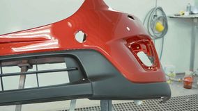 Car bumper after painting in a cars spray booth. Vehicle cherry color bumper stock image
