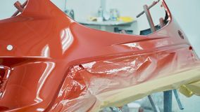 Car bumper after painting in a cars spray booth. Vehicle cherry color bumper royalty free stock photography