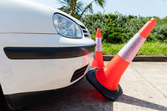 Car bumping traffic cones. White car bumping the traffic cones Royalty Free Stock Photography