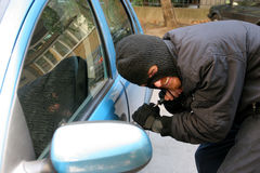 Car burglary. Burglar wearing a mask (balaclava), car burglary Stock Photography