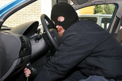 Car burglary. Burglar wearing a mask (balaclava), details car burglary inside Stock Photo