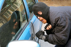 Car burglary. Burglar wearing a mask (balaclava), car burglary Royalty Free Stock Photo