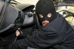 Car burglary. Burglar wearing a mask (balaclava), details car burglary inside Royalty Free Stock Photography
