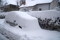 The car, bushes and houses covered with snow Royalty Free Stock Images