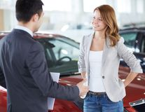 Car buyer. Successful young lady discussing her potential purchase with a car dealer Stock Photography