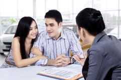 Car buyers discussing with car dealer. Picture of two young car buyers discussing with a female car dealer in the showroom Stock Images
