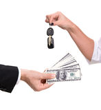 Car buying. Female hand holding a car key and handing it over to another person.Man holding dollars Stock Photo