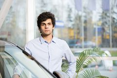 Car buying. Young handsome man at show room standing near car Stock Photography