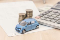 Car with calculator and money on wood table. auto loan concept.  royalty free stock images