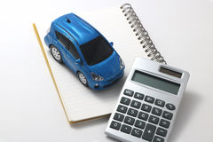Car, calculator, and notebook Stock Images