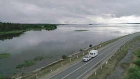 A car with a camper trailer rides along a dam across river in Canada. Landscape