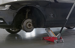 Car on car jack. Detail of car on car jack with tire removed Stock Photos