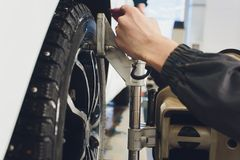A Car on the Car Steering Wheel Balancer and Calibrate with laser reflector attach on each tire to center driving adjust. In the garage royalty free stock image
