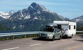 Car and caravan. Car with caravan driving on a coastal road under the mountains Stock Photos