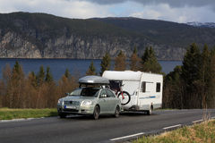 Car and caravan. Car with caravan driving on a coastal road under the mountains Stock Images