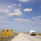 Car and Caravan Australia. Car and caravan on the Eyre Highway, Nullarbor Plain, including iconic sign look out for camels, kangaroos, wombats. This part of the royalty free stock images