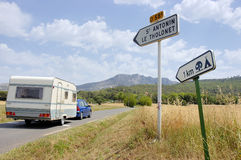 Car with caravan at road. Car with white caravan at road with at right hands signs to the camping Stock Images