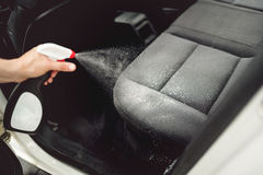 Car care concept, detailing and cleaning car interiors. Worker spraying cleaning solution on car upholstery. Car care concept, detailing and cleaning car Stock Photo