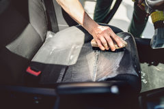 Car care concept, detailing and cleaning details. Worker using cleansing techonology for upholstery. Car care concept, detailing and cleaning details. Worker Royalty Free Stock Photo