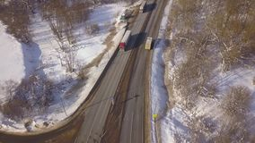 Car and cargo truck moving on winter highway view from above flying drone. Aerial view car traffic on snowy road on. Winter landscape stock video footage