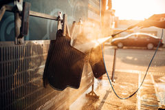 Car carpets washing with high pressure washer. Car-wash station Royalty Free Stock Photography