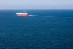 Car Carrier and Ocean Aerial View. A car carrier cargo ship sails a deep blue vast ocean, leaving a think wake behind. Horizontal image with deep vessel stock photography