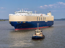 Car Carrier Ship and Tug Boat Stock Image