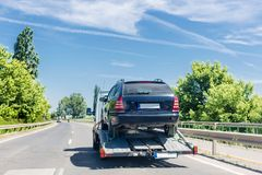 Car carrier trailer with car. Car transported on evacuation tow truck on highway royalty free stock photos