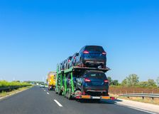Car carrier trailer with cars on bunk platform. Car transport truck on the highway. Space for text royalty free stock image