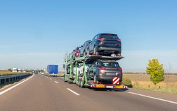 Car carrier trailer with cars for sale on bunk platform on the highway royalty free stock photos