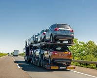 Car carrier trailer with cars on bunk platform. Car transport truck on the highway royalty free stock image