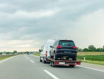 Car carrier trailer with new car on highway stock image