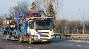Car carrier truck deliver new auto batch to dealer Stock Photos